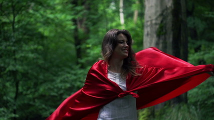 Mysterious woman in red cape on stairs in forest, slow motion