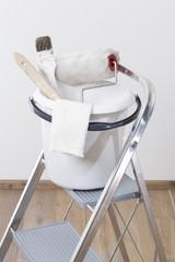 Farbeimer mit Pinsel, Farbroller, und Tuch auf Leiter