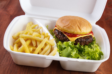 Burger and fries portion in takeout food box