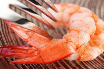Cooked shrimps with fork closeup on glass plate