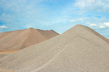 Sand heaps with blue sky in gravel quarry