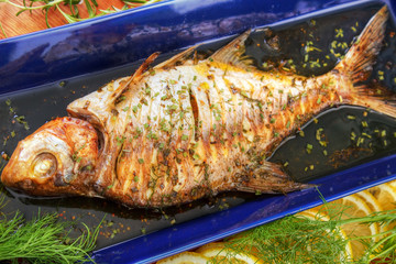 Oven cooked fish with herbs on blue fish platter
