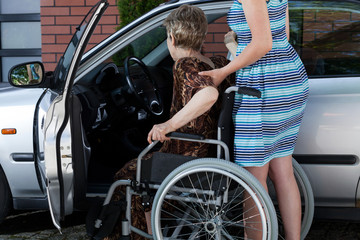 Woman helping a disabled lady get in the car