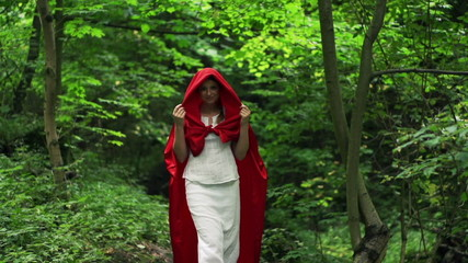 Mysterious woman in red cape walking in forest, slow motion