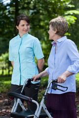 Elderly woman walking with a walker