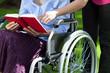 Leinwanddruck Bild - Close-up of an elderly woman in a wheelchair reading a book