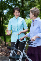 Nurse encourages older woman for walking