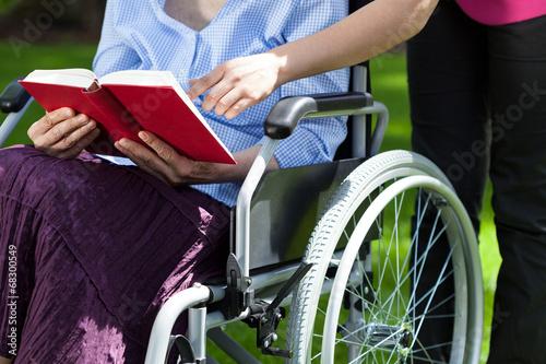 Leinwanddruck Bild Close-up of an elderly woman in a wheelchair reading a book