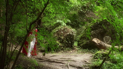Beautiful red riding hood walking in forest, super slow motion