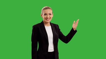 Young businesswoman with megaphone on green screen.