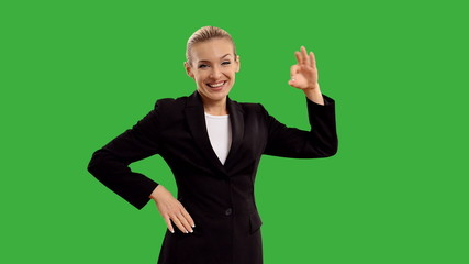 businesswoman presenting and show sign okay  on green  screen.