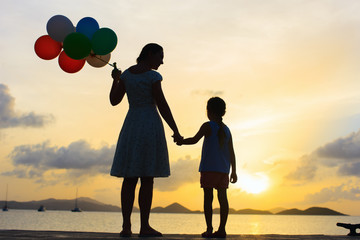 Happy family with balloons at sunset