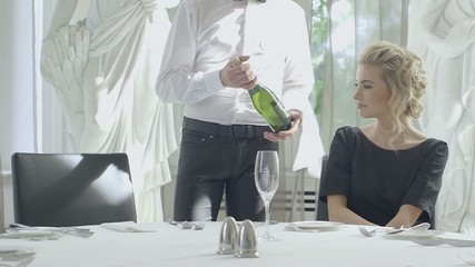 Young blonde woman selecting wine in luxury restaurant table