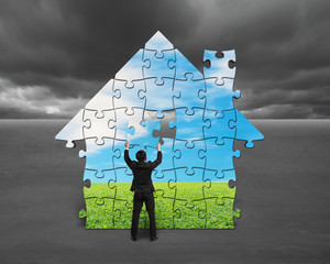 Businessman assembling house shape puzzles with nature image