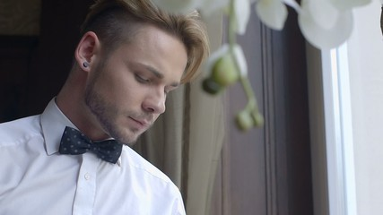 Closeup of a pensive waiter selecting a champagne bottle