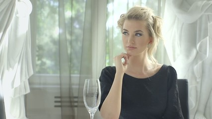Attractive blonde woman waiting at the restaurant table