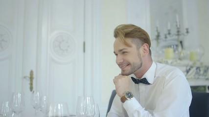 Attractive smiling man in luxury restaurant during conversation