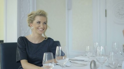 Attractive smiling blonde woman in a luxury restaurant