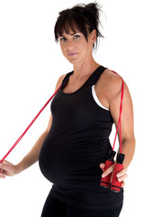 Pregnant model working out with a jump rope