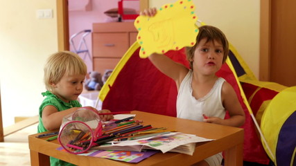 Two children sketching with paper and pencils in home