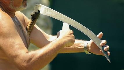 sharpening scythe in hot summer day