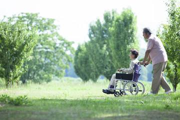 車椅子で散歩をする夫婦