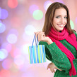 Beautiful young woman with gift bag on bright background