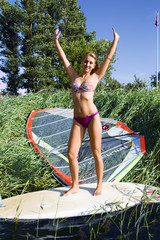 Slender blonde is glad to engaging in windsurfing