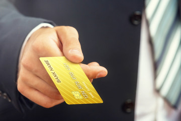 Close up of a businessman`s hand,holding gold credit card.