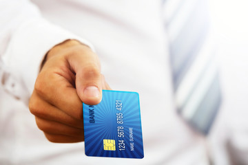Close up of a businessman`s hand,holding blue credit card.