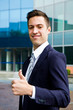 Young smiling confident man doing thumbs up sign outside office