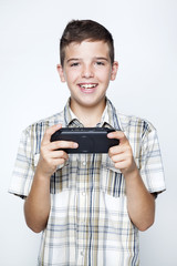 A teen boy playing video games in a portable game console agains