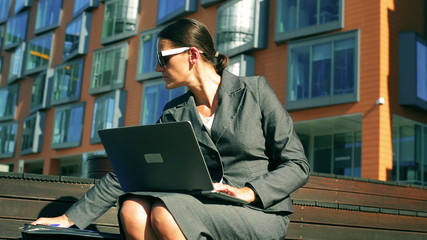 Businesswoman working on laptop and documents