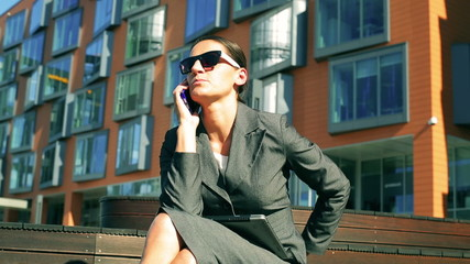 Businesswoman talking on cellphone in front of modern building