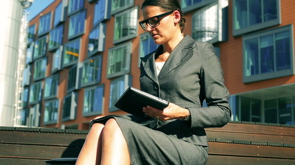 Businesswoman working on tablet in front of modern building