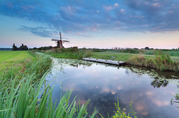 windmill by river at sunset