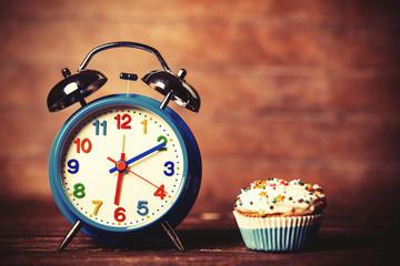 Alarm clock and cupcake.