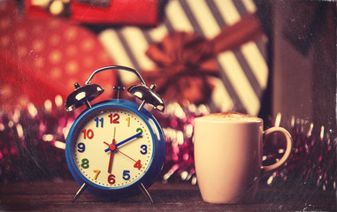 Vintage clock and cup of coffee on christmas background