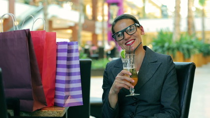 Businesswoman relaxing after shopping and smiling to the camera