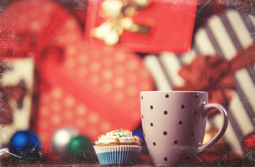 Cup of coffee and cupcake on christmas background.