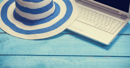 Laptop and hat on blue wooden table.