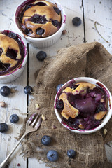 clafoutis with blueberries and cherries on rustic background