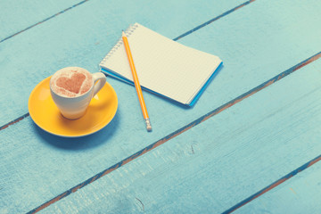 Cup of coffee with heart shape and pencil with notebook