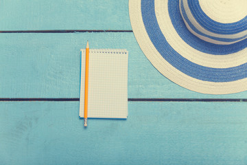 notebook with pencil and hat on blue wooden table