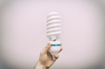 Hand holding big energy efficient fluorescent lamp.