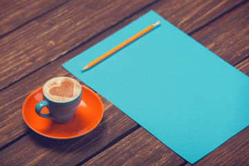 Cup of coffee and pencil with paper.