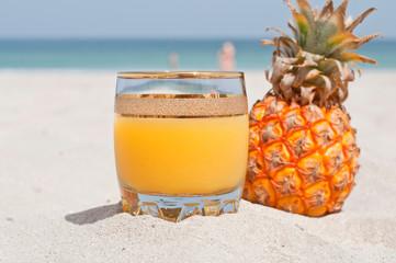 Glass of pineapple juice on a beach