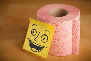 Post-it note with smiley face sticked on a toilet paper
