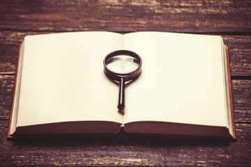 opened book and loupe on a table.