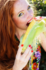 Smiling girl with freckles holding corn cob